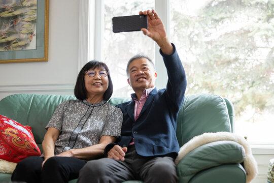 Senior couple taking selfie on sofa