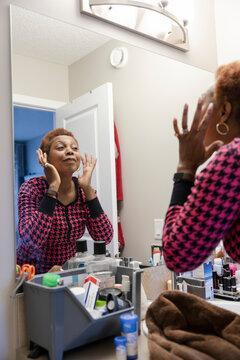 Senior woman wearing pyjamas looking at bathroom mirror