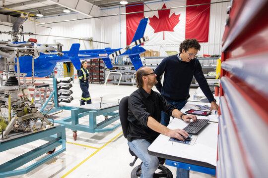 Men looking at computer in helicopter hangar
