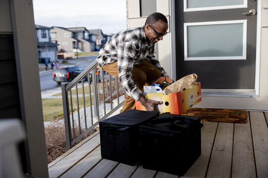Smiling senior man carrying box of groceries on porch