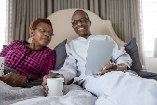Senior couple relaxing using digital tablet on bed