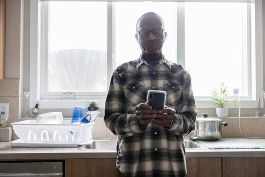 Portrait of senior man texting on phone in kitchen