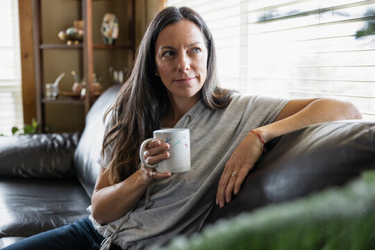Portrait of smiling woman with hot drink on sofa