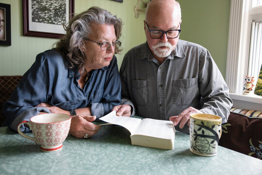 Senior couple reading book at dining table