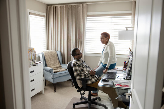 Senior couple talking in home office