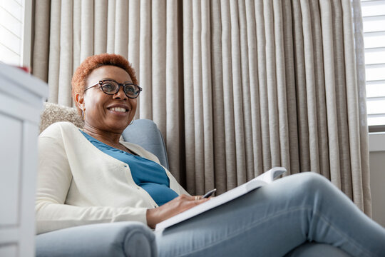 Smiling senior woman with book in armchair