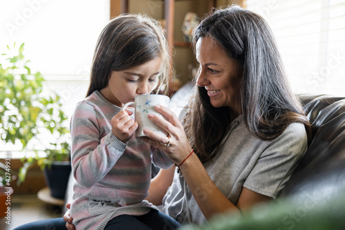 Girl drinking on mother's lap