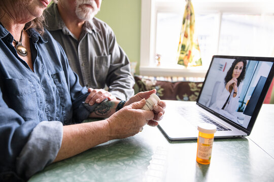 Doctor consulting with senior couple on video call