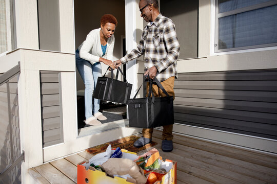 Senior couple carrying bags of groceries into house