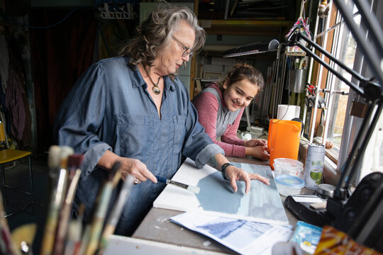 Grandmother and granddaughter painting in studio