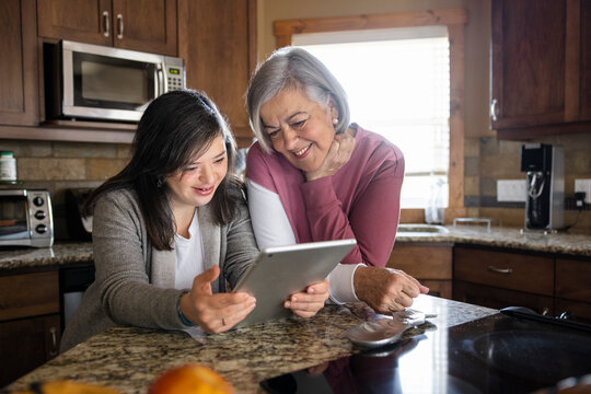 Senior woman and daughter with down syndrome using digital tablet