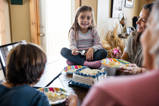 Portrait of smiling girl sitting on table at birthday party