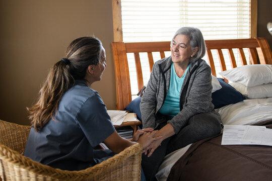 Nurse comforting senior woman on bed