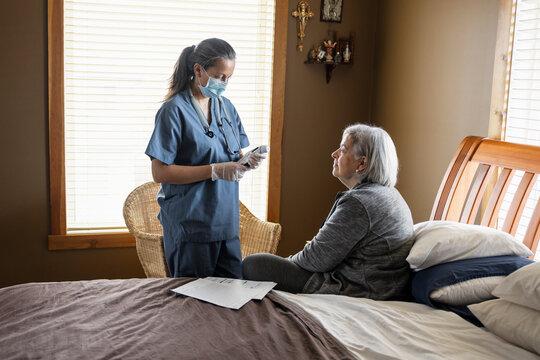 Nurse wearing facemask taking temperature of senior woman in bedroom