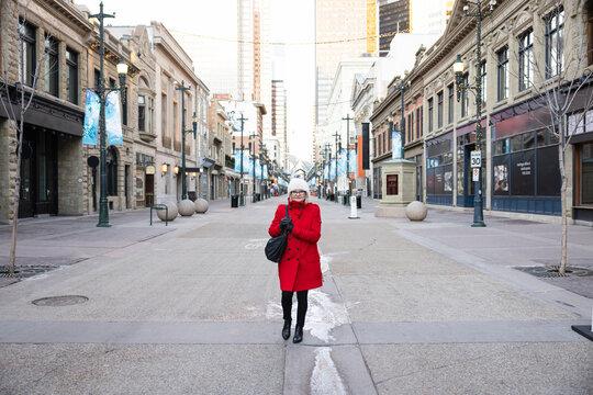 Portrait senior woman in winter coat on empty city street