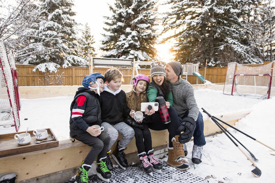 Happy affectionate family taking selfie at backyard ice hockey rink