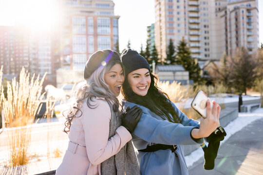 Happy young women friends taking selfie in sunny urban winter park