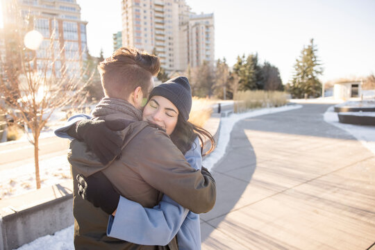 Affectionate young couple hugging on path in sunny urban winter park