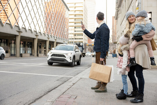 Family with shopping bag waiting for crowdsourced taxi on city street