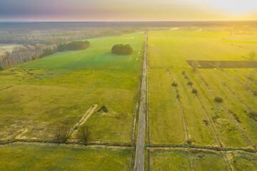 Asfaltowa droga przebiegająca przez rozległą równinę. Widok z drona.