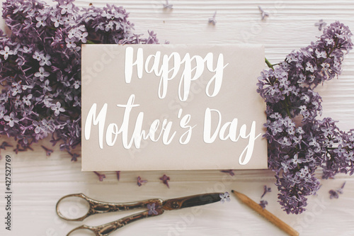 Happy mother's day. Happy mother's day text on card and lilac flowers, vintage scissors, pencil on white rustic wood top view. Stylish floral greeting card. Handwritten lettering. Mothers day