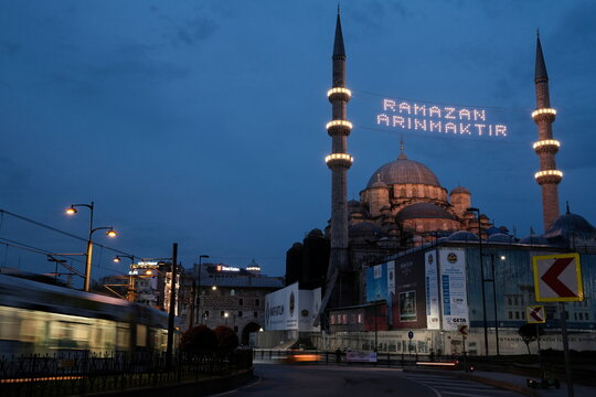"""A mahya reading """"Ramadan means being purified"""" hangs between the minarets of the Ottoman-era Eminonu New mosque in Istanbul"""