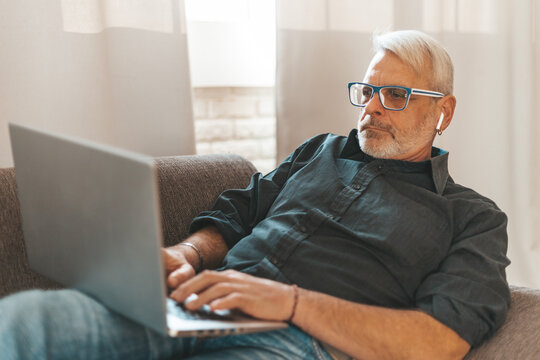 Focused on work at home. An adult man is watching a video on a laptop and is lying on the couch. Remote work, a pensioner uses a computer.