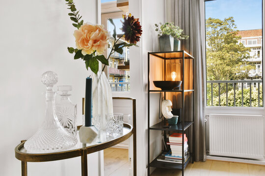 Table with glassware and flowers and bookcase with books and decorations placed near doorway and window in light room at home