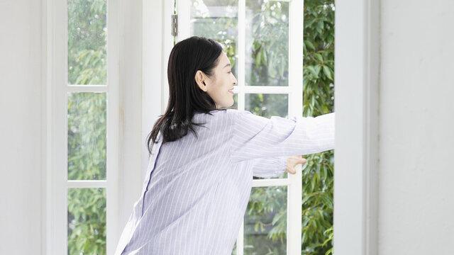 窓を開け換気する笑顔のミドル女性