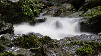 Closeup shot of cascades of a fast-flowing stream on the mountain rocks Wall mural