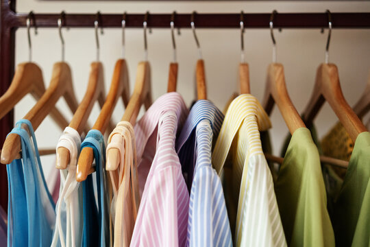 Beautiful clothes in delicate pastel colors hang on hangers in a row, fashion trends concept