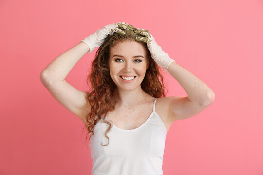 Young woman using henna hair dye on color background