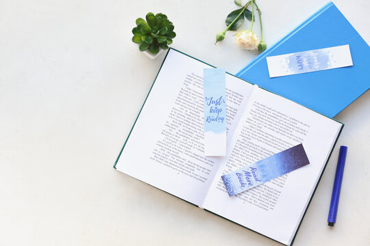 Books with bookmarks and flower on light background