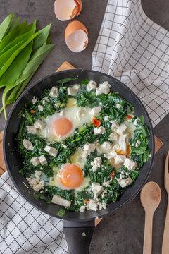 Green shakshuka. Fried eggs with wild garlic and feta cheese