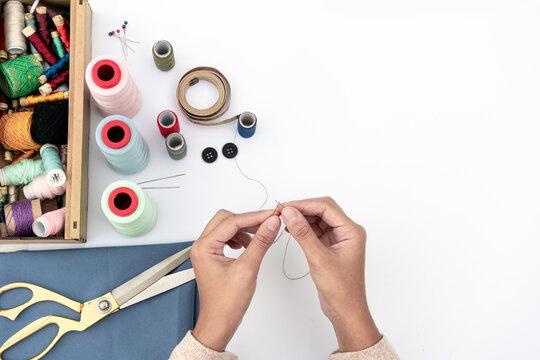Costura. Manos de mujer enhebrando aguja de coser. Herramientas de costura.  Manualidades. Hilos. Agujas. Botones. Tijera. Alfiler.  Accesorios. Plantilla con espacio para texto