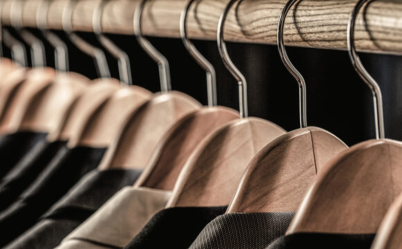 Mens suits in different colors hanging on hanger in a retail clothes store, close-up. Mens shirts, suit hanging on rack. Hangers with jackets on them in boutique. Suits for men hanging on the rack