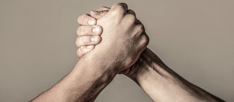 Arms wrestling. Closep up. Friendly handshake, friends greeting, teamwork, friendship. Handshake, arms, friendship. Hand rivalry vs challenge strength comparison. Man hand. Two men arm wrestling