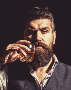 Man drinking whiskey, brandy, cognac. Degustation, tasting. Man with beard holds glass of brandy. Tasting and degustation concept. Bearded businessman in elegant suit with glass of whiskey