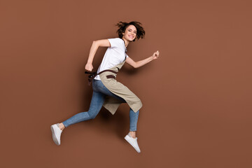 Full length profile photo of carefree pretty girl rush look camera toothy smile isolated on brown color background Wall mural