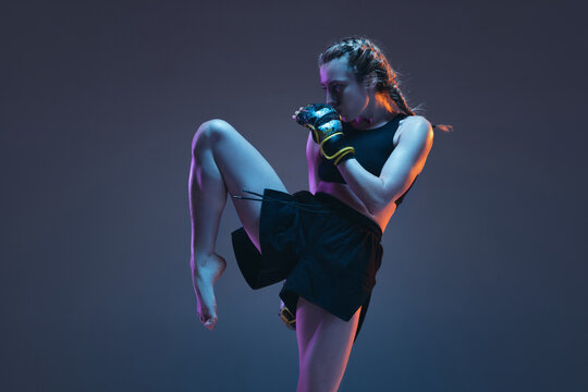 Caucasian female MMA fighter training isolated on blue background in neon light