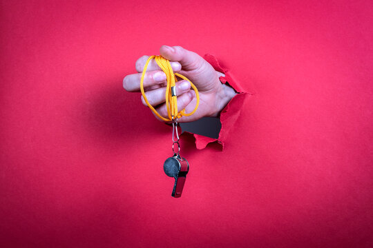 Metal whistle in a woman's hand. Bright red background