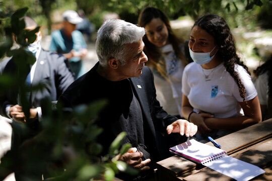 Yair Lapid, leader of Yesh Atid party, speaks to a youth during a visit to a memorial site on Israel's Memorial Day in southern Israel