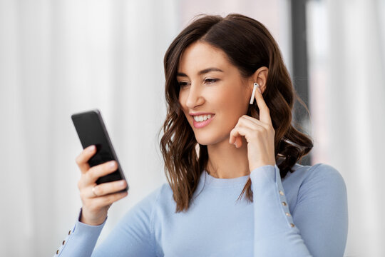 people, technology and leisure concept - happy young woman with wireless earphones and smartphone listening to music at home