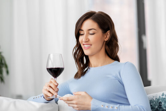 leisure and people concept - happy woman drinking red wine at home