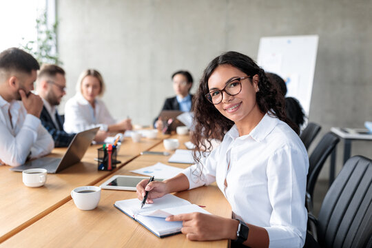 Businesswoman Taking Notes Smiling To Camera At Corporate Meeting Indoor