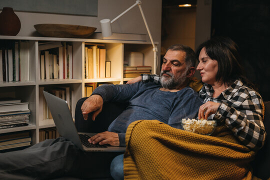 middle age couple using laptop computer at home. evening scene