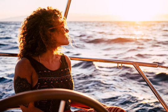 Cheerful attractive young adult blonde woman smile and enjoy the excursion trip sitting on the sail boat deck looking the blue sea around - concept of summer adventure people
