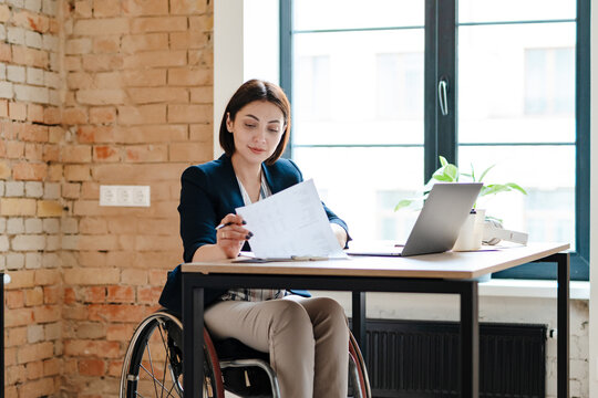 White young woman in wheelchair working with papers and laptop