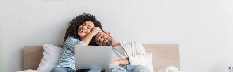 Fototapeta cheerful interracial couple resting in bed near laptop, banner