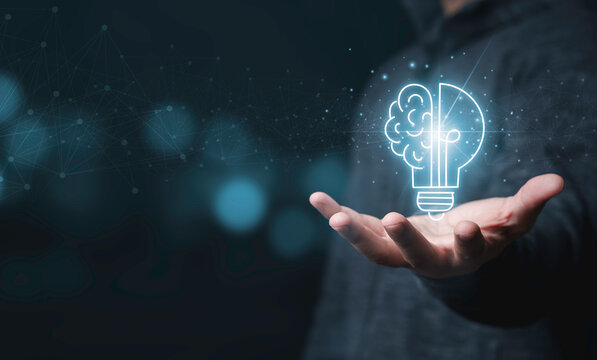 Businessman holding half of virtual lightbulb and brain on blue bokeh background , Smart thinking idea and inspiration innovation concept.